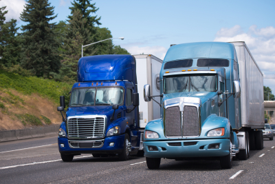 two blue trucks on the road